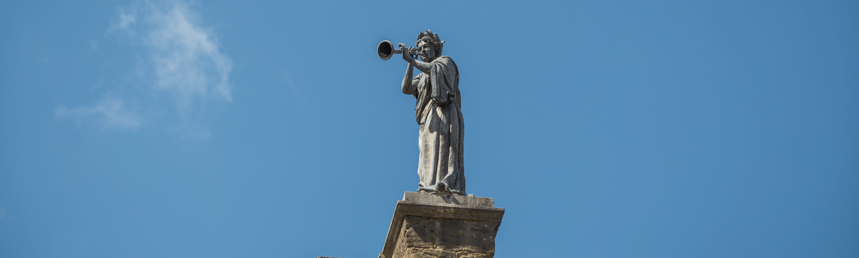 Statue of a woman against blue sky
