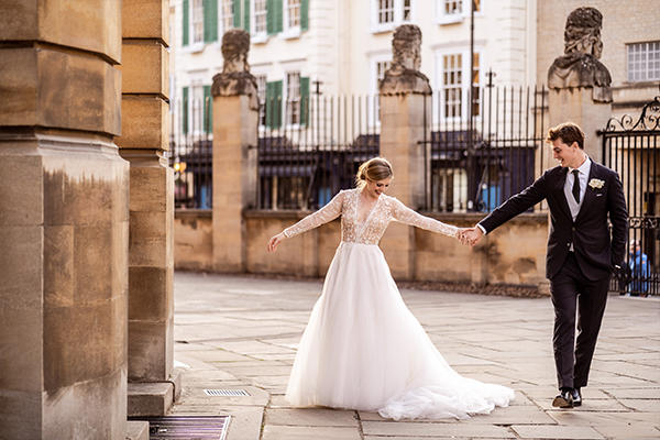 Bride and Groom holding hands outside the Sheldonian Theatre