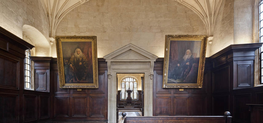 Two paintings in gilt frames hanging on a panelled wall either side of a stone doorway