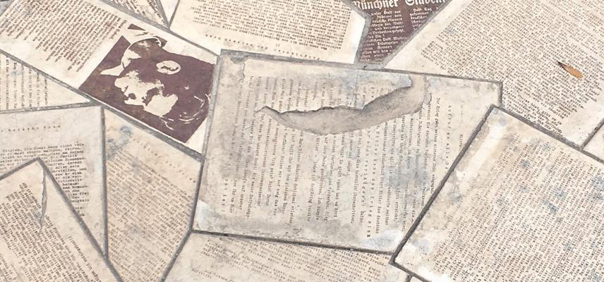 Newspaper cuttings on a stone floor